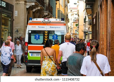 Verona, Italy - June, 16, 2018: The ambulance car breaks through crowd of tourists in Verona