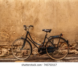 VERONA, ITALY - June 25, 2017:  Verona.  Retro styled image of vintage old  Bicycle on Street in Italy, parking near wall with copy space.