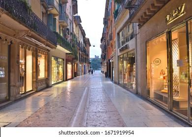 VERONA, ITALY - MARCH 12: Deserted via Mazzini, Verona's main shopping street, during lockdown due to Corona virus. Closed shops and bars during the Covid-19 virus pandemic.