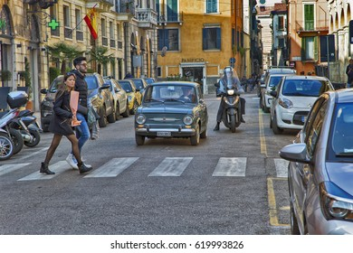 Verona, Italy - March, 4, 2017: A pedestrian crossing across a small street.