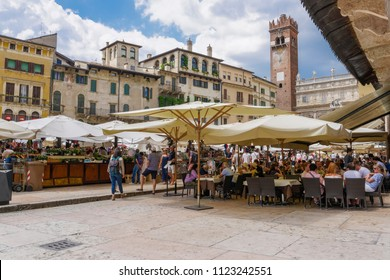 Verona, Italy - May 11 2018: Piazza delle Erbe traditional buildings. Crowd eating beside open air market stalls on Market square restaurants.
