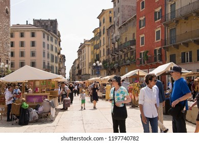 VERONA, ITALY - May 6, 2018: Tourists in Market at Piazza Erbe in the sunny day. Traditional market at Piazza Erbe in Verona attracts many tourists and shoppers.