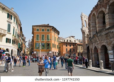 VERONA, ITALY - May 6, 2018: Tourists in Piazza Bra in sunny day.  Piazza Bra is the largest square in Verona and place where the well-preserved ancient Roman amphitheater is located.