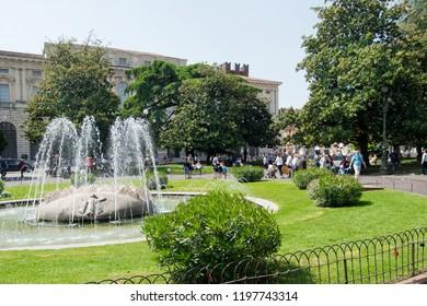 VERONA, ITALY - May 6, 2018: Tourists in Piazza Bra in sunny day.  Park on Piazza Bra in Verona is a popular spot providing shade in hot sunny days