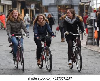 Verona, Italy - November 20, 2018: Three happy girls on bicycles biking on the street.