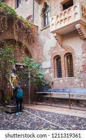 Verona, Italy - October 2018: A woman holds the hand of Juliet's statue (of Shakespeare's Romeo and Juliet) at the courtyard outside Juliet's house