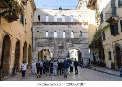 Verona, Italy - October 5, 2018: Tourists by the medieval gate Porta Borsari in the city of Verona in Italy