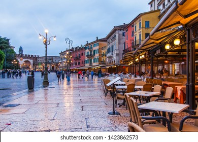 Verona, Italy, on April 27, 2019. People go along Piazza Bra Square, one of central squares of the city in the evening after a rain. Tables of picturesque street cafe under an awning.
