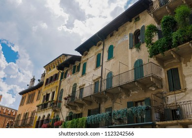 Verona, Italy Piazza delle Erbe buildings. Day view of traditional houses with balconies at Market square.