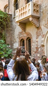 """VERONA, ITALY - SEPTEMBER 2018: Person taking a picture of Juliet's balcony on the House of Juliet or """"La Casa di Giulietta"""", a major tourist attraction in Verona."""