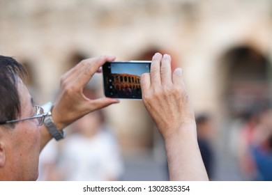 Verona, Italy - September 5, 2018: Asian tourist taking a photo of the famous Verona Arena, a Roman amphitheatre in Piazza Bra in Verona, built in the first century. Selective focus