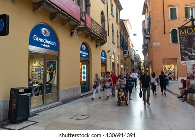 Verona, Italy - September 5, 2018: Crowd walking on a pedestrian street in front of a GrandVision store, a global leader in optical retail