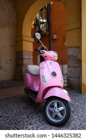 VERONA, LOMBARDY, ITALY - 03 July 2019: pink Vespa motorbike parked on the streets of Verona city