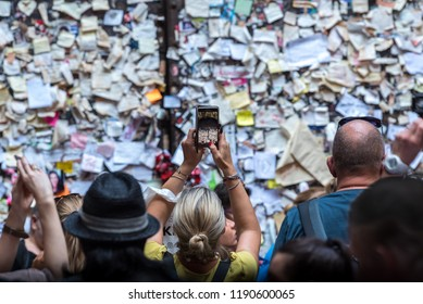 Verona, Veneto, Italy - September 15 2018: Tourist takes a picture with smartphone of sticky post-it notes and heart locks left by visitors on wall nearby Romeo and Juliet's balcony, selective focus