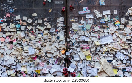 Verona, Veneto, Italy - September 15 2018: Sticky post-it notes and heart locks left by tourists and visitors on wall nearby sculpture of Juliet and Romeo and Juliet's balcony