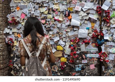 Verona, Veneto, Italy - September 15 2018: Young woman looks at sticky post-it notes and heart locks, memories left by tourists and visitors on wall nearby Romeo and Juliet's balcony, selective focus