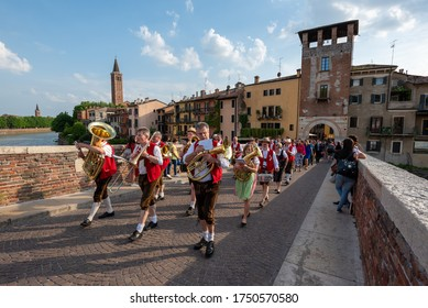 Verona (VR) / Italy - April 28, 2018: A marching band crosses the Ponte Pietra in Verona, Italy.
