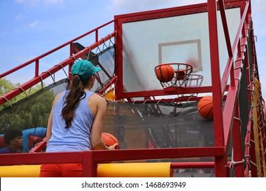 Verona, WI / USA - June 16, 2018: Woman playing a miniature basketball game at a company picnic