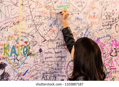 Verona,Italy. - June 2. 2018The girl writes the name on the wall near the balcony of Juliet in Verona, the whole wall is full of declarations of love and names (not logos) in different languages