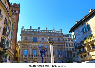 Verona,Veneto/Italy-July 18 2018:A view of Piazza delle Erbe-Narket square in Verona with the ancient fountain and  the statue called Madonna Verona and  Torre dei Lamberti maintained façade frescoes