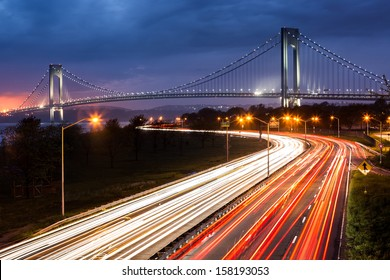 Verrazano Narrows Bridge above the light trails of the Belt Parkway traffic.