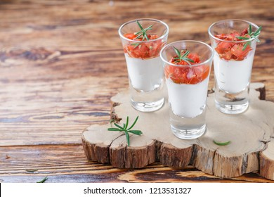 Verrines appetizer with cream cheese (ricotta) and tomato salad in small glasses with rosemary and spices. Portioned snack gourmets. Panna cotta. Selective focus