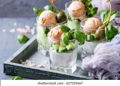 Verrines appetizer with salmon pate, red caviar, cucumber, cream cheese, herbs, capers in glasses served on wooden tray with pink salt and basil over blue gray texture background. Close up