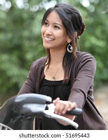 Verry pretty young asian woman on bike smiling while commuting/biking to work