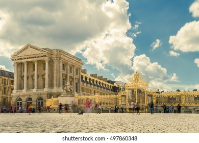 Versailles chateau. France. View of golden gate to palace. Royal residence near Paris. King's quarters. Famous touristic renaissance architecture landmark in summer. Toned