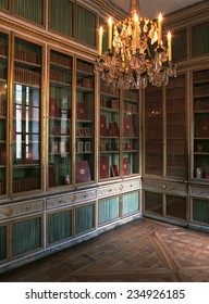 Versailles, France - 10 August 2014 : Large bookshelf and chandelier at Versailles Palace ( Chateau de Versailles ). It was added to the UNESCO list of World Heritage Sites.