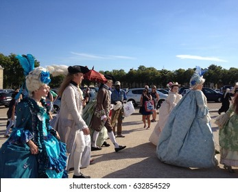 Versailles, France - 27 June 2015: Guests arrive for the The Grand Masked Ball at the Palace of Versailles. People in full 18th century costume walk up to the gates of the Palace of Versailles.