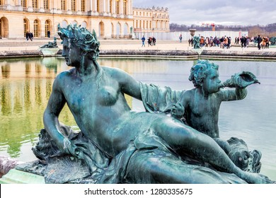VERSAILLES, FRANCE - January 2, 2019. Palace of Versailles. Park and bronze statue Nymph and Child at the conch.