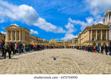 Versailles, France - MAY 2019: View of a large U-shaped queue of visitors at Versailles Palace at the golden royal gate in the cobblestoned court of honour (cour d'honneur) with pigeons in the centre.