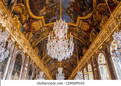 VERSAILLES, FRANCE - SEPTEMBER 29, 2018: Beautifuul crystal chandelier hanging from the decorated ceiling inside the Versaille Palace. Expensive historical decorations