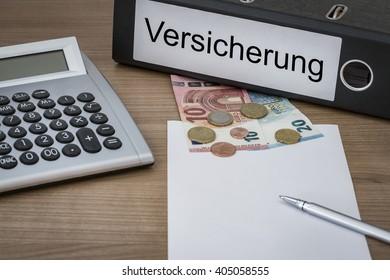 Versicherung (German Insurance) written on a binder on a desk with euro money calculator blank sheet and pen