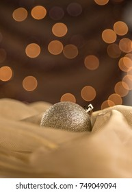 Vertical Abstract Warm Gold Glitter Sparkle Christmas Ornament On Shiny Fabric Bokeh Background. Selective Focus With Copy Space.