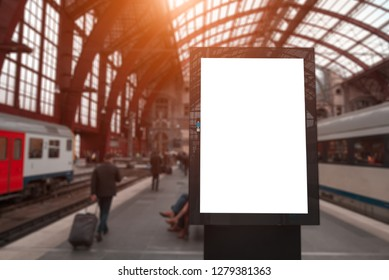 Vertical advertising billboard with empty mockup on train station near people.