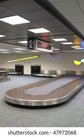 """Vertical Airport Baggage Claim Carousel.  Some carts on the left, top reads """"Welcome to"""". Carousel is empty, before the bags are unloaded"""
