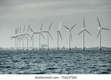 Vertical axis wind turbines generator farm for renewable sustainable and alternative energy production along coast baltic sea near Denmark. Eco power, ecology.