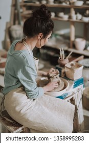 Vertical back view portrait of charming craftswoman kneading and shaping clay in pottery workshop