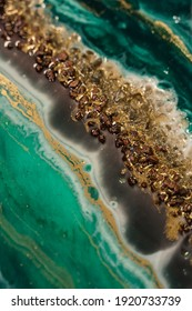 vertical background modern abstract design made with epoxy resin. gold powder and a mixture of different shades of green paint creating the effect of sea water and sandy shore