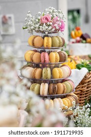 Vertical beautiful macaron cake patisserie multi tier stand full French macaroons all flavours colours at real wedding with flowers roses pink strawberry yellow brown chocolate cookies pyramid tower