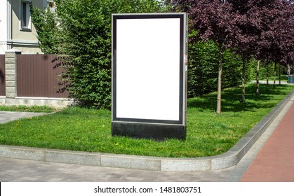 Vertical billboard or citylight mockup template commercial advertisement standing on the grass near trees and a house in a small European cozy town outdoor street sunny summer day, no people