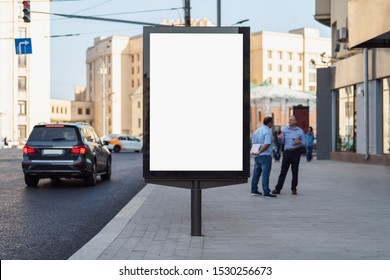Vertical billboard near road in public place. Blank screen for commercial ad of companies and marketing agencies. Multi-laned urban street with traffic lights. Office workers communicating, talking.