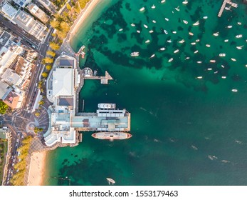 Vertical bird's eye aerial evening drone view of Manly wharf, part of the oceanside suburb of Manly, Sydney, New South Wales, Australia. Two ferries docked at the wharf.