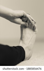 Vertical black and white detail of yogini wearing long dark yoga pants making forward bending exercise on the floor, reaching foot and touching toes with hand. Indoor home yoga practice in sepia tone