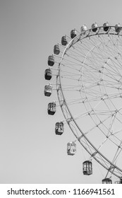 A vertical, black and white photo of a giant, classic Ferris wheel rising high into the sky.