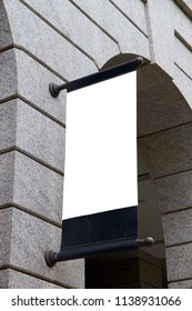 A vertical blank advertising mockup of placard is suspended on the facade of the vintage marble  European styled architecture.