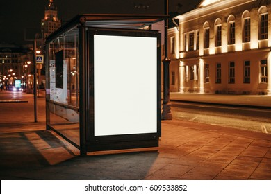 Vertical blank glowing billboard at bus stop on the night city street. In the background buildings and road. Mock up. The poster on the street next to the roadway.