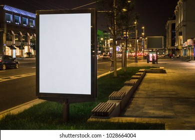 Vertical blank glowing billboard on night city street. In background buildings and road with cars. Mock up. Light box on street next to roadway. Space for logo, text, image, advertising, ad, blurb.